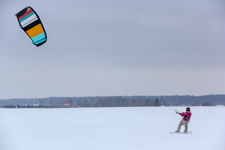 Girl Snowboarder Rides With Kite. Snowkiting in Winter.