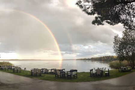 Double Rainbow Over Lake in Latvia. Cafe Table With Chairs in the Background. Stockfoto
