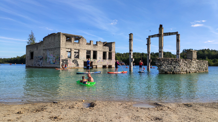 Sand Hills of Quarry With a Pond and Abandoned Prison in Rummu Estonia Europe. Flooded Houses of Former Prison. Mountain in the Abandoned Mines Sunken Ruins of Soviet Time Prison Architecture.