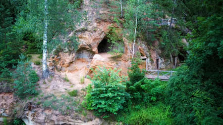 Sandstone Caves in Ligatne, Latvia. View to Cave Rock Lustuzis (Lustūzis) on the Bank of Ligatne River. Caves With Old Wooden Doors.