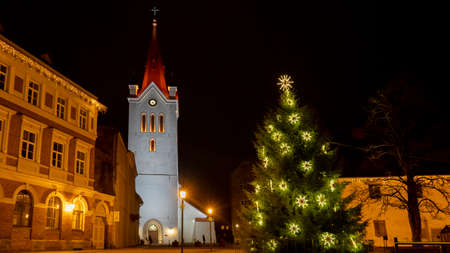 Ancient St. John`s Church at Night Located in Cesis, Latvia. Cesis Medieval Castle and City in Background. Cristmas Time Night Shot.