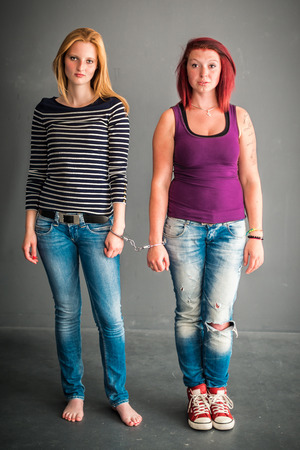 female prisoner: Two angry women connected by a pair of handcuffs, blond and red-haired, wearing jeans, barefoot and red chucks on grey background Stock Photo