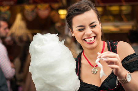 dirndl dress: Beautiful young smiling woman wearing a traditional Dirndl dress with cotton candy floss at the Oktoberfest.