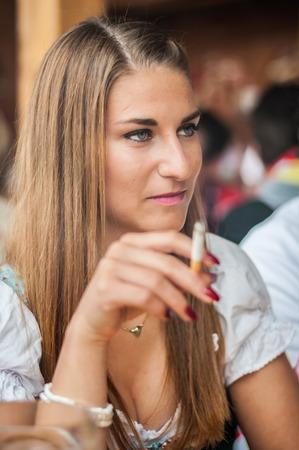 person smoking: Mujer joven hermosa en Dirndl o un vestido tracht estar y fumar en el Oktoberfest