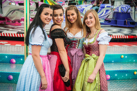 joyride: Joyful young and attractive women at German funfair Oktoberfest with traditional dirndl dresses and joyride in the background. Mixed nationalities.