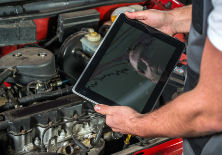 motor mechanic: Mechanic using a tablet pc at the repair garage, red automobile Stock Photo