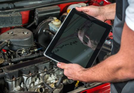Monteur met behulp van een tablet-pc op de reparatie garage, rode auto