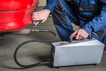 A diagnostic sensor is applied to the ehaust of a red car, measuring the composition and substances in the exhaust fumes in a garage