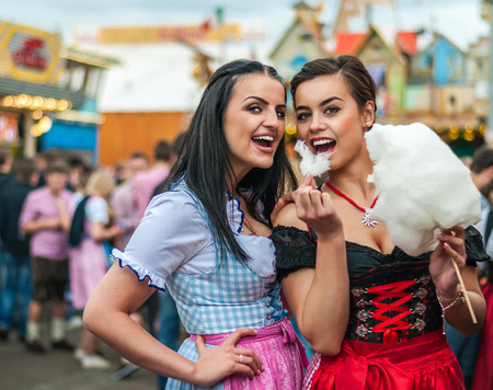 tracht: Two young women in traditional Bavarian clothes, dirndl or tracht, laughing with cotton candy floss at the Oktoberfest