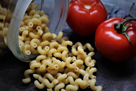 An image of dark pasta with tomatoes Stock Photo