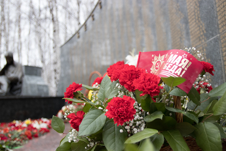 red flag with red carnations on the monument, victory day, editorial, Khanty-Mansiysk, may 9, 2017