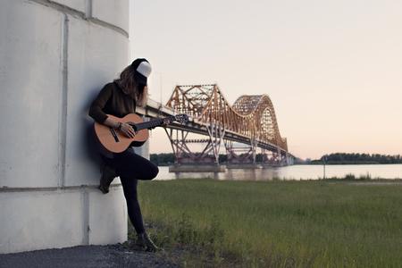 ギターを弾く川に架かる橋の支えの少女