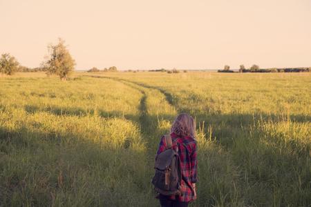 背の高い草の野原の真ん中で田舎道を歩く肩にバックパックを持つチェック柄のシャツの女の子 写真素材