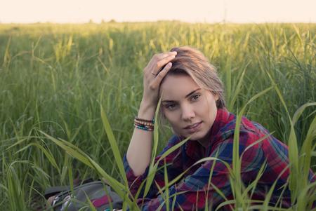 夕焼けの光の中で野原の背の高い草の中に座っている女の子