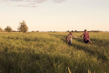 女の子のカップルは、背の高い草と大きなフィールドの泥道に行く