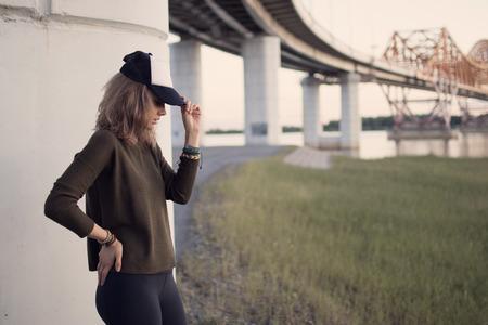 日没と背の高い草とフィールドでプロファイルで帽子の女の子の肖像画 写真素材