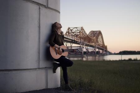 川に架かる橋のふもとにギターを持った少女 写真素材