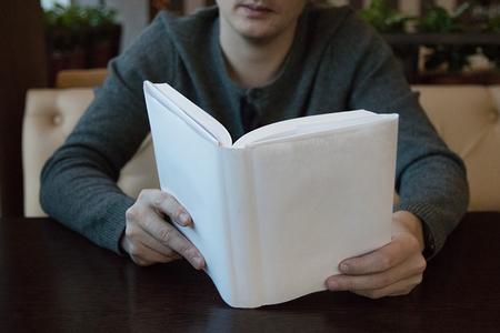 カフェのテーブルで白い表紙の本を読んでいる男 写真素材