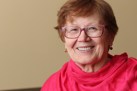 ピンクの明るいスカーフとサングラスを着用した笑顔の老婦人の肖像 写真素材