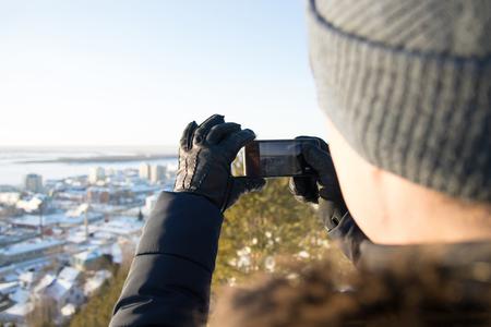通りの服を着た男は、冬の街の写真を撮る電話 写真素材
