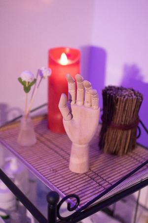 金属製のスタンドに木製の手、ろうそく、お香の棒や装飾的な花の配置 写真素材