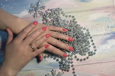 hands with neat manicure on bright background with silver-tone beads and snowflakes on wooden boards Stock Photo
