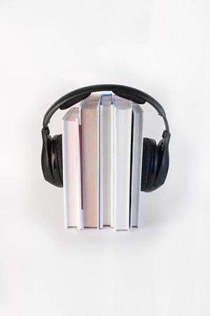 それらの上に垂直に白い背景に5冊の本は、ヘッドフォンを囲みます