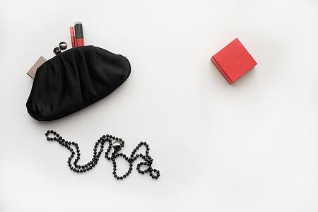 女性クラッチハンドバッグブラック、化粧品のセット(口紅、パレット、ブラシ)、白い背景に装飾品やジュエリーを持つボックス 写真素材