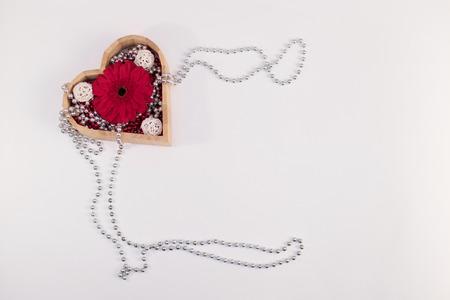 白い背景にビーズと花ガーベラと赤い箱と他のアイテムと木製のボックスのハート形状