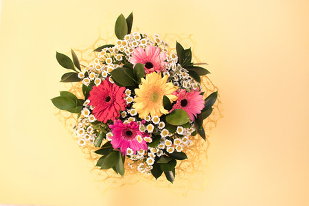 黄色の背景に小さなヒナギクと多色のガーベラからの花の花束