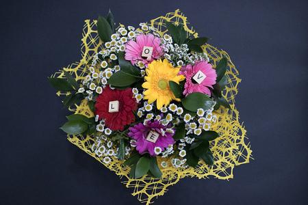 黒い背景に小さなヒナギクと大きなカラフルなガーベラからの花の花束