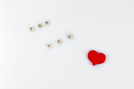 白い背景に文字と木製の赤いハートを持つキューブ