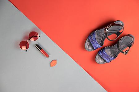 赤と青灰色の背景に女性の靴、アクセサリーや化粧品 写真素材