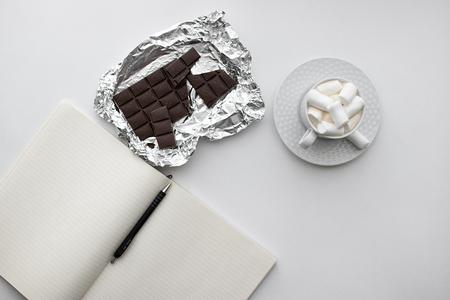 白い背景ノートの上のビュー, ペン付きメモ帳, ドリンクとマシュマロのカップ, チョコレート