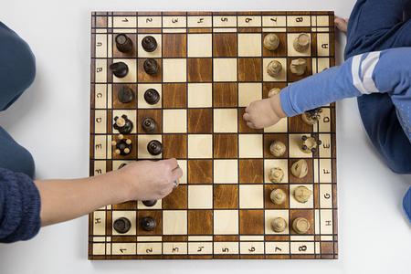 白い背景でチェスをしている子供と大人のトップビュー