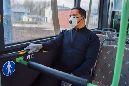 passenger with mask wears protecting gloves on his hands in bus to protect himself from the coronavirus epidemic is alone in bus