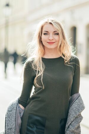 Close up portrait of young blond beautiful woman walking on city street, europe vacation, holding little bouquet, smiling, walk in krakow, grey coat, beautiful young woman walking on the street Imagens