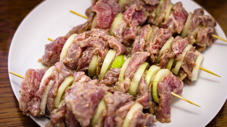 Cooking Meat. Onions And Tomatoes Dance Around The Frying Pan, Then A Plate Of Sliced Meat Appears In The Picture. The Meat, Onion And Tomatoes Stretched Over A Wooden Skewer Are Ready To Roast. Banco de Imagens
