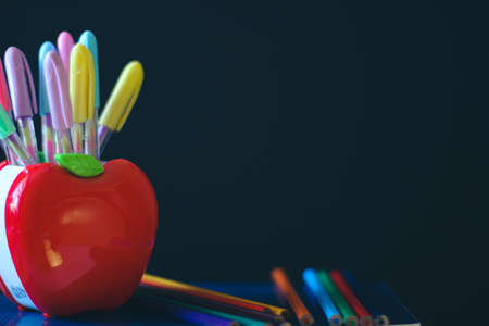 School accessories. Multicolored Pencils Stand at the stands in the shape of an apple. In Background of a dark school board and a piece of chalk. On the board is a place for a copy space.