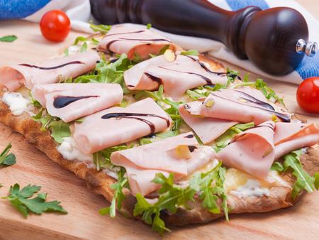 klassische leckere italienische Pizza Mortadella mit Rucola und Mozzarella auf Holzuntergrund