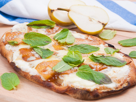 classic sweet Italian pizza with pear and mozzarella cheese on a wooden Board
