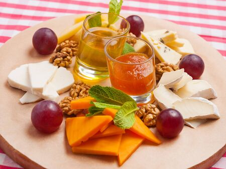 tasty cheese platter with walnuts, honey and grapes on a wooden Board