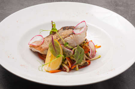 tasty grilled pike perch fillet with vegetables and lemon