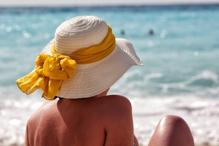 a girl with sun hat that see sea photo