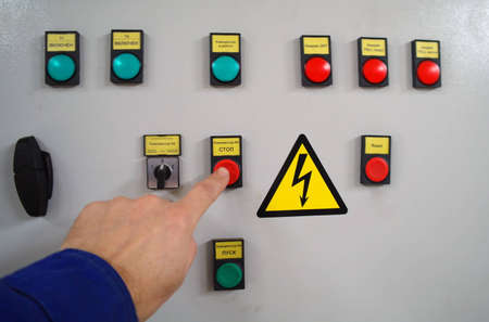 Onoff buttons and a control led in a black electric box against a white wall near a metal conductors tube  photo