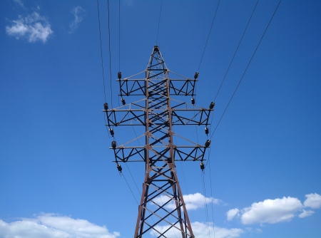 Electricity pylon against blue cloudy sky photo