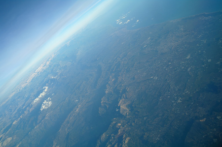 Aerial view above clouds and landscape.
