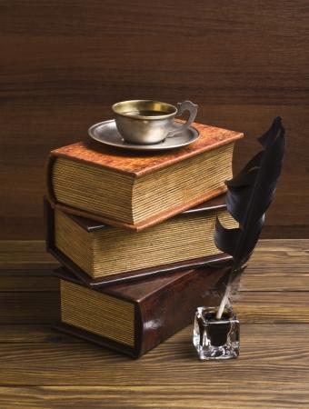 pluma de escribir antigua: libros antiguos y pluma en una mesa de madera Foto de archivo