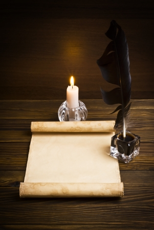 scribe: feather, old paper and candle on a wooden background Stock Photo