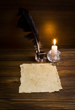 feather, old paper and candle on a wooden background Standard-Bild